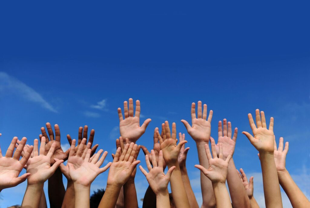A mixture of hands from people of different colours, representing diversity and inclusion.